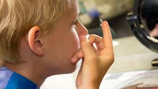 Ребенок надевает линзы